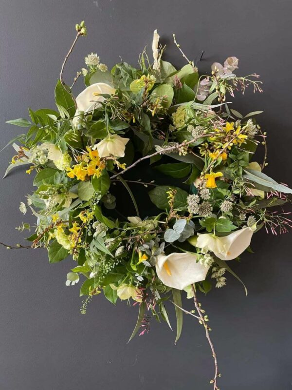 The photo showcases an floral wreath, with beautiful foliage and florals. Wreath is sat on a dark grey wall to show contrast.